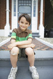 Happy Boy Sitting On Front Steps Of House Stock Photography