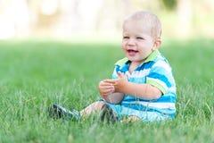 Happy boy sitting on green lawn Royalty Free Stock Photos