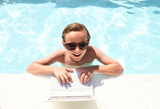 Happy boy sitting with laptop in swimming pool Stock Images