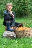 Happy boy sitting near basket full of chanterelles Stock Photos