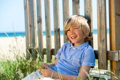 Happy boy sitting next to fence on beach. Royalty Free Stock Image