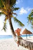 Happy boy sitting on palm Royalty Free Stock Image