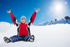 Happy boy sitting on sled on sunny day. Happy exited boy sitting on sled with her hands lifted,, in the mountains Stock Image