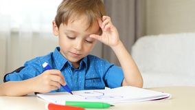 Happy boy sitting at the table and fun draws colorful pens. The child spends time for creativity. stock footage