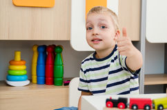 Happy boy sitting at table and showing thumb up gesture. Boy finger thumb up gesture kindergarten ok sitting concept Stock Image