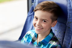 Happy boy sitting in travel bus or train. Transport, tourism, road trip and people concept - happy boy sitting in travel bus or train Stock Photos