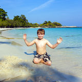 Happy boy sitting at a tropical beach Stock Image