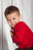 Happy boy sitting. Young boy sitting in chair in studio, smiling with red shirt and wood background Royalty Free Stock Image