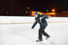 Happy boy skates with arms outstretched. Happy boy wearing in black suit skates with arms outstretched at winter night stock image