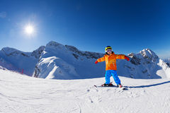 Happy boy in ski mask with arms apart skiing alone Stock Photo