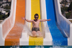 Happy young waterslider. Happy boy is sledding on colorful waterslide in aquapark Stock Images