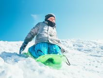 Happy boy slides down from snow hill using the sledge. Winter outdoor activity stock image