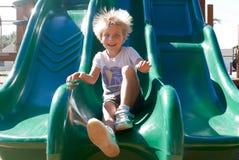 Happy boy sliding down a slide royalty free stock photos
