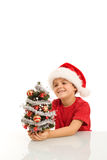 Happy boy with small christmas tree and santa hat Royalty Free Stock Photo