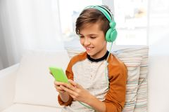 Happy boy with smartphone and headphones at home royalty free stock photography