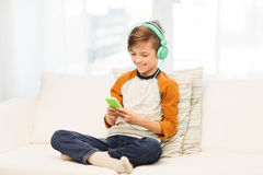 Happy boy with smartphone and headphones at home Stock Image