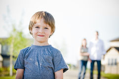 Happy boy smiling. Young boy smiling with parents in background Stock Photos