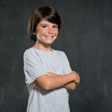 Happy boy smiling. Closeup shot of little boy standing with armcrossed  on blackboard. Portrait of kid smiling and looking at camera. Pride little boy in casual Stock Images