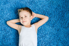 Happy boy smiling kid looking at camera on blue carpet in living room at home Stock Photo