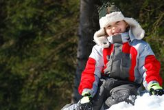 Happy boy on snowbank. A view of a happy, smiling boy sitting on top of a snowbank on a sunny winter day Royalty Free Stock Image