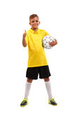 A happy boy with a soccer ball and in a football uniform isolated on a white background. Full-length photo. A smiling footballer with a soccer ball and a thumb Royalty Free Stock Photography