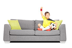 Happy boy with a soccer ball sitting on a sofa and gesturing hap. Happy boy in sportswear with a soccer ball sitting on a sofa and gesturing happiness isolated Royalty Free Stock Images