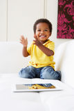 Happy Boy On Sofa Playing With Digital Tablet Royalty Free Stock Image