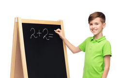 Happy boy solving math on school blackboard. Childhood, education, school, advertisement and people concept - happy smiling boy in green polo t-shirt solving Royalty Free Stock Photos