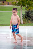Happy boy in splash pad Royalty Free Stock Images