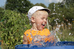 Happy boy and splashes of water Stock Photography