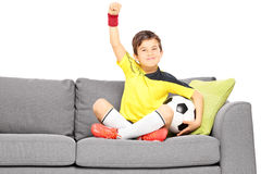 Happy boy in sportswear with a football sitting on a sofa and ge Royalty Free Stock Images