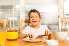 Happy boy spreading chocolate with knife on toast. Portrait of smiling boy spreading chocolate with a knife on his toast sitting at a table in the kitchen stock images