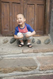 Happy boy squat. Chinese happy boy squat ahead wooden door Royalty Free Stock Image