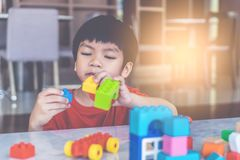 Boy stacking Toy blocks on a living room for educational toy stock photo