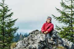 Happy boy standing on cliff Stock Photos