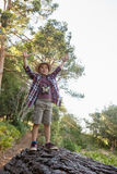 Happy boy standing on the fallen tree trunk. In the forest Stock Images