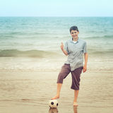 Happy boy standing with a football on a beach Stock Photo