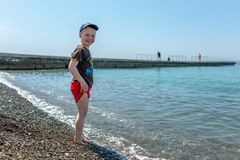 Happy boy standing in front of the sea on a beach royalty free stock image