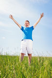 Portrait of the boy on a meadow. Happy boy standing on a green meadow Royalty Free Stock Photo