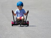 Happy boy standing on hoverboard or gyroscooter with kart access. Ory kit outdoor. New modern technologies royalty free stock images