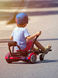 Happy boy standing on hoverboard or gyroscooter with kart access Royalty Free Stock Images