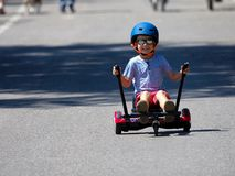 Happy boy standing on hoverboard or gyroscooter with kart access. Ory kit outdoor. New modern technologies royalty free stock image