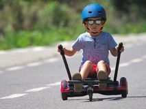 Happy boy standing on hoverboard or gyroscooter with kart access. Ory kit outdoor. New modern technologies stock photos