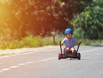 Happy boy standing on hoverboard or gyroscooter with kart access. Ory kit outdoor. New modern technologies stock images