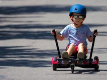 Happy boy standing on hoverboard or gyroscooter with kart access. Ory kit outdoor. New modern technologies stock photo