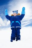 Happy boy standing with sled with lifted hands Stock Photo