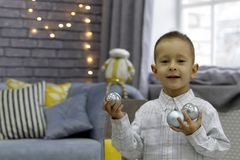 Happy boy, standing in a stylish room, holds balls in both hands at Christmas royalty free stock image