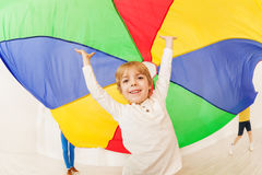 Happy boy standing under parti-colored parachute. Portrait of happy preschool boy standing under the tent made of parti-colored parachute with his hands up Royalty Free Stock Photography