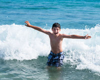 Happy boy standing in water Royalty Free Stock Image