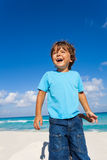 Happy boy stands on sandy beach of ocean coast Royalty Free Stock Photos